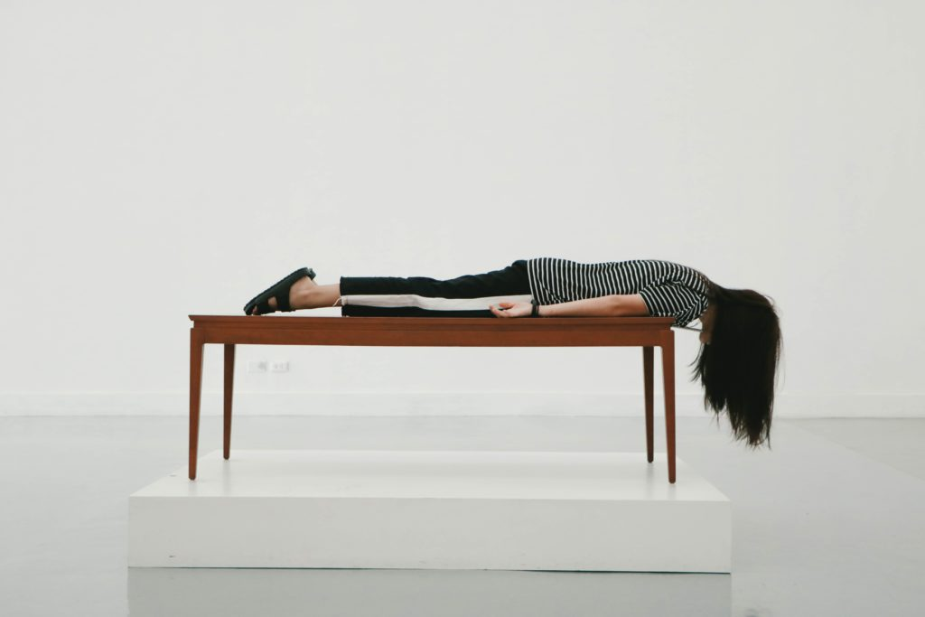 A woman lying upside down off of a table